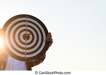 Man hand holding a target with darts hitting the center. Concept of business target.