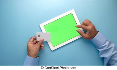 Man hand holding credit card and using digital tablet hopping online .