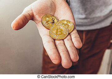 Man hand holding cryptocurrency golden bitcoin coin. Electronic virtual money for web banking and international network payment. Symbol of crypto virtual currency. Mining concept.
