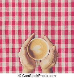 Man hand holding cup coffee on red and white fabric.