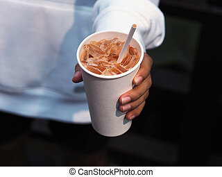 man hand holding disposable white recycling glass of cold cappuccino coffee
