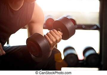 Man hand holding dumbbell exercise in gym. Fitness muscular body with set of black weights in the gym background. exercise and healthy lifestyle concept.
