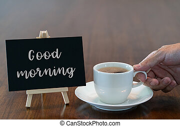 Man hand holding hot coffee cup in the morning