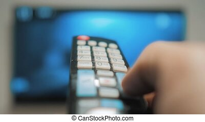 man hand holding lifestyle the TV remote control and turn...