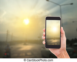 Man hand holding mobile phone with sunset background