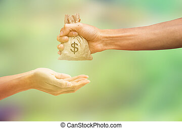 Man hand holding money bag and giving money to another person on blurred green nature background. Money concept. Conceptual paying for exchanges