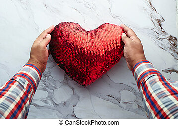man hand holding red heart on white background