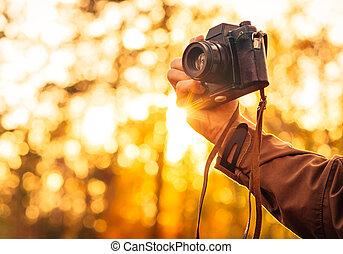 Man hand holding retro photo camera outdoor Lifestyle...