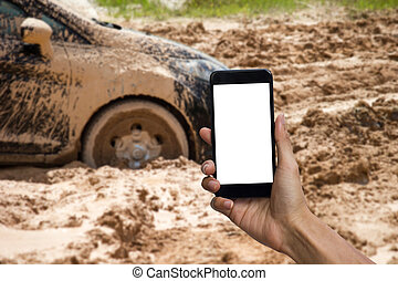 Man hand holding smartphone with white screen display use for mock up. Car tire stuck in the mud background. Car wheel in the mud clay can not run out.