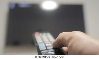 man hand holding the TV remote control and turn off smart...