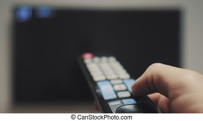 man hand holding the TV remote control and turn off smart tv...
