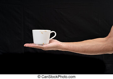 Man hand holding white coffee cup on black background