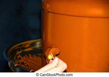 Man hand holds a fruit on a stick in a chocolate fondue fondue