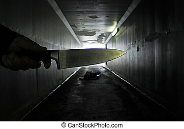Man hand holds a knife over a murder victim in a dark...
