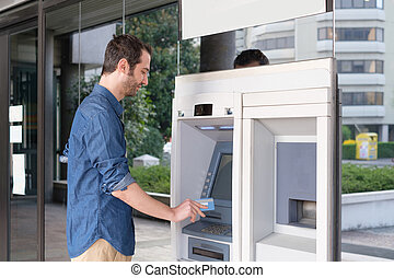 Man hand inserting a credit card in an atm