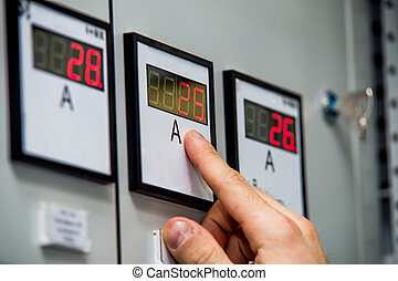 Man hand on ammeter close-up. Control of energy system...