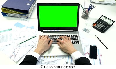 Man hand on laptop keyboard with green screen monitor in the office