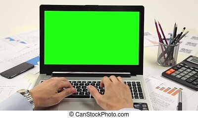 Man hand on laptop keyboard with green screen monitor