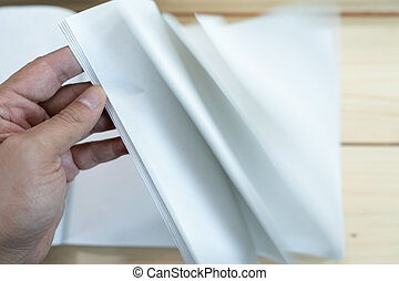 man hand open the white empty notebook on the wood table.