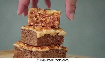 Man hand pick up piece of almond caramel coffee cake