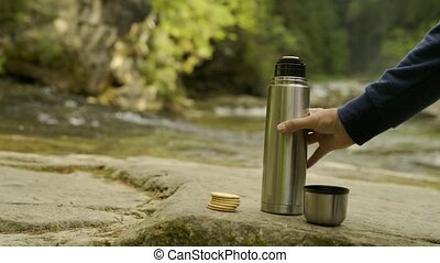 Man hand pouring hot drink into a mug from the thermos, in...