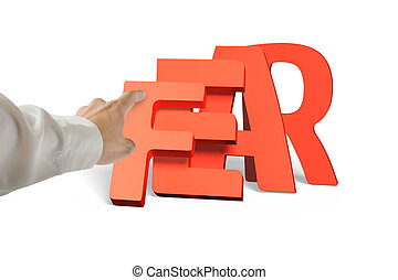 Man hand pushing domino of red fear word falling