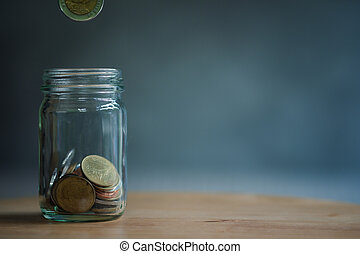 Man hand put Thai coin in to jar glass.