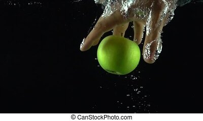 Man hand reaches and grabs green apple floating in water super slow motion shot