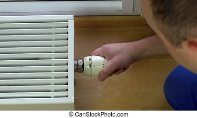 man hand reduce warm by radiator thermostat in room. 4K