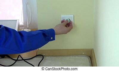 Man hand remove plug wire from outlet and insert child...