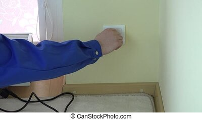 Man hand remove safety plug from wall socket and insert plug...