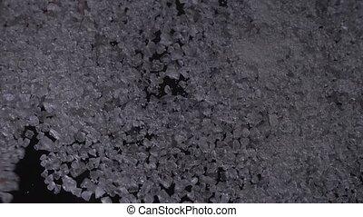 Man hand removing coarse salt pile, black background clip