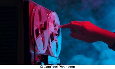 Man hand rotates reels on old analogue reel to reel audio tape recorder. Vintage music player on a blue smoky studio background with red neon lights. Close up. Slow motion