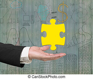 Man hand showing one 3D gold jigsaw puzzle piece