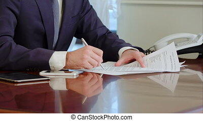 Man hand signs a paper document with ballpoint pen. Signature is fake.