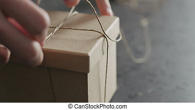 man hand ties bow on brown paper box