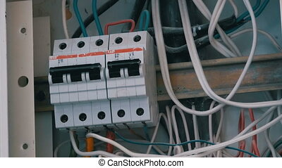 man hand turns on and off electricity power fuse circuit in the panel