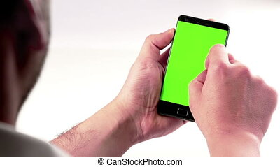 man hand using a smart phone with chroma key on white background behind view, green screen, lifestyle communication with smartphone technology concept