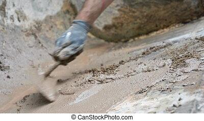 Man hand using trowel to mix mortar. - Man hand using trowel...