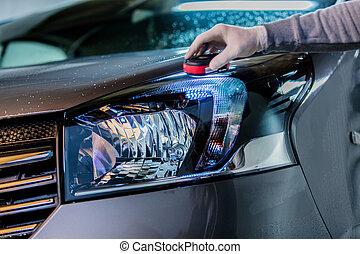 washing a car headlight on carwash