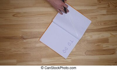 man hand writing to do list on notepad, top view