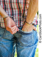 man handcuffed outdoors in the park