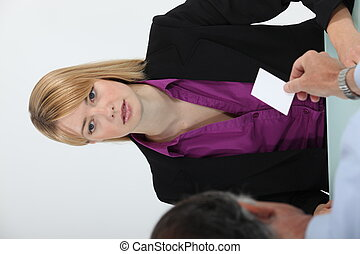 Man handing business card to woman