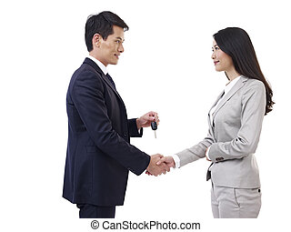 man handing car key to woman