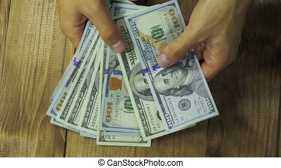 Man Hands Consider Dollar Banknotes on a Wooden Table. Money...