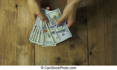 Man Hands Consider Dollar Banknotes on a Wooden Table.