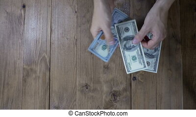 Man Hands Consider Dollar Banknotes on a Wooden Table. Slow...