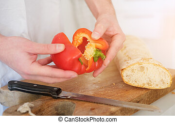 Man hands cutting pepper slices in the kitchen
