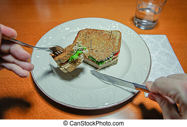 Man hands cutting sandwich with fork and knife - Closeup of...