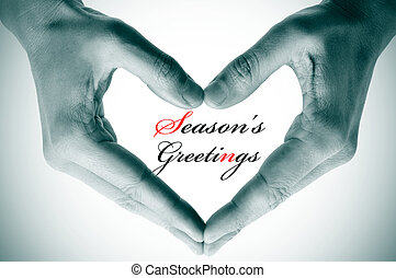 seasons greetings - man hands forming a heart and the ...
